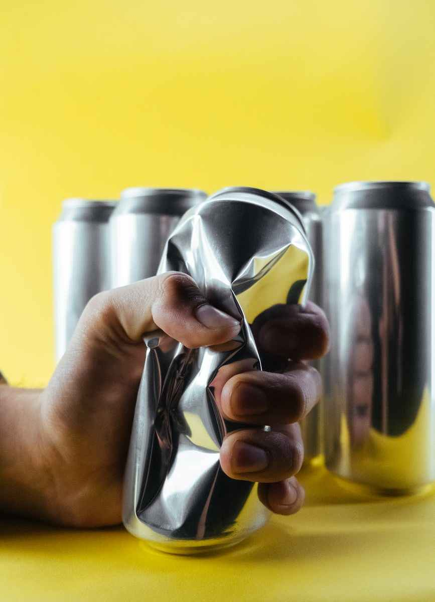 person pouring yellow liquid on stainless steel cup