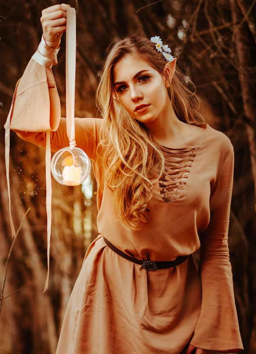 woman wearing brown long sleeved shirt holding round glass terrarium