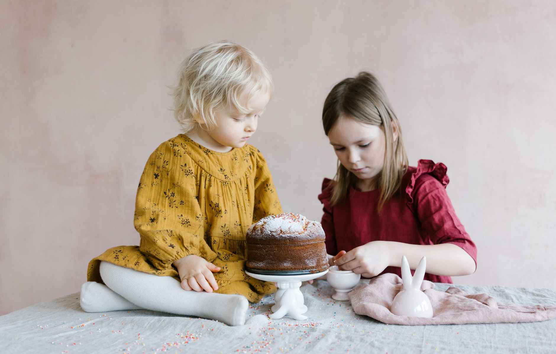 girls sitting at table with easter cake