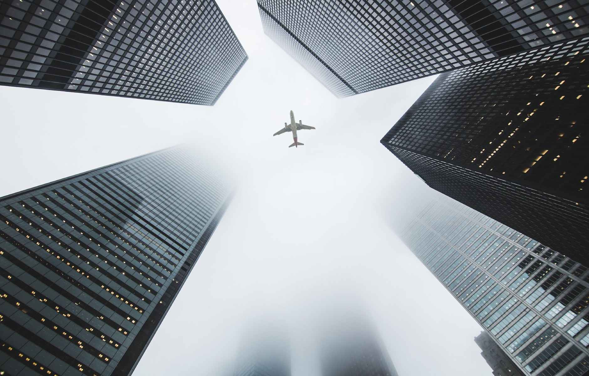 low angle photo of airplane flying over high rise buildings