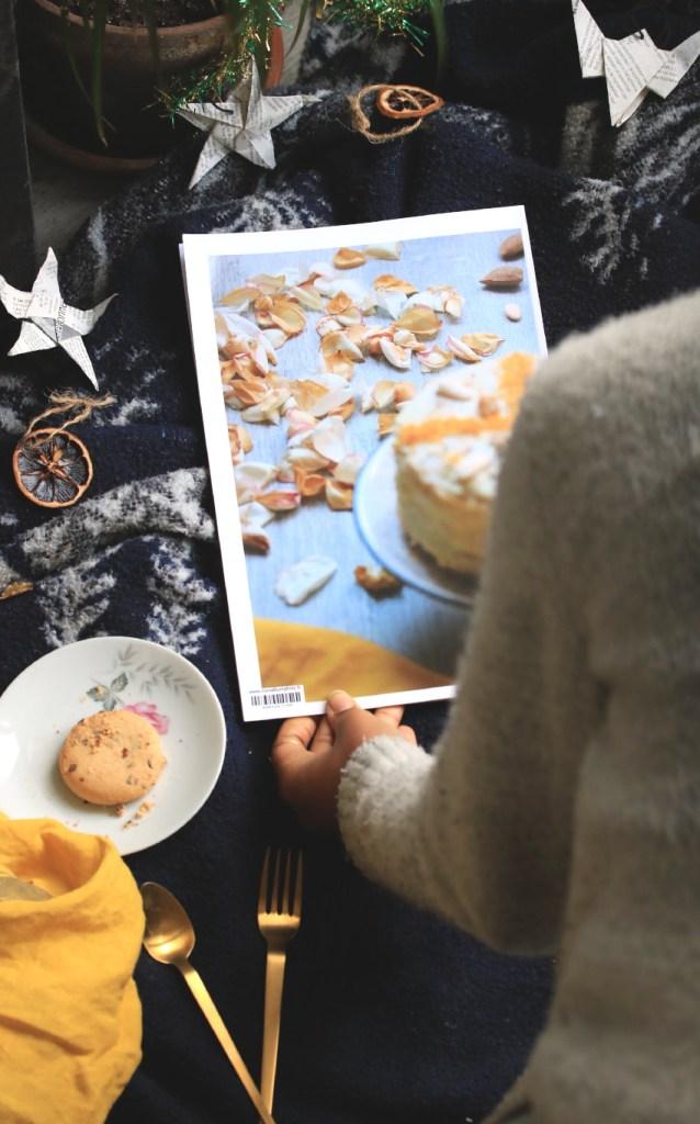 j'ai sous la main un livre de photos culinaire de pâtisserie posé sur une couverture bleu marine à côté d'une assiette qui contient un cookie