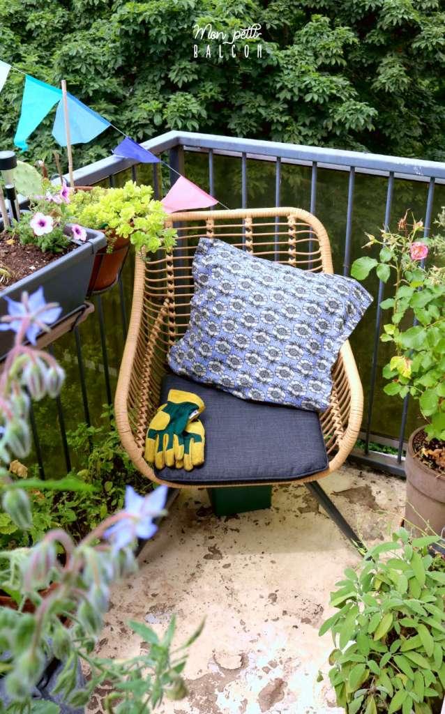 chaise de jardin en rotin et coussin bleu posé sur le balcon
