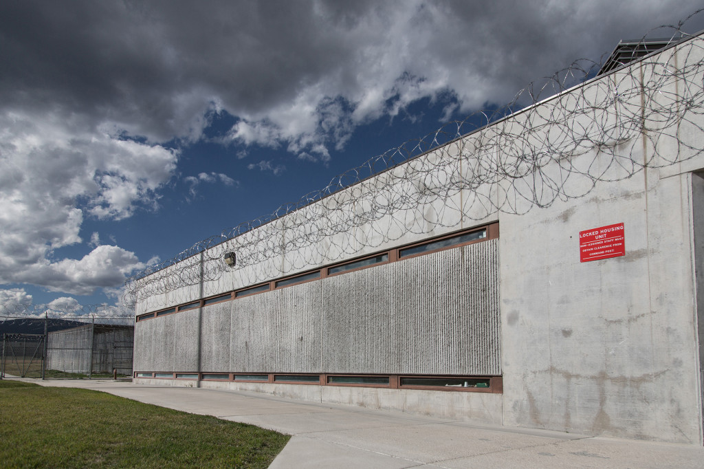 A razor-wire fence surrounds a windowless concrete building that serves as one of the locked housing units at the Montana State Prison in Deer Lodge.