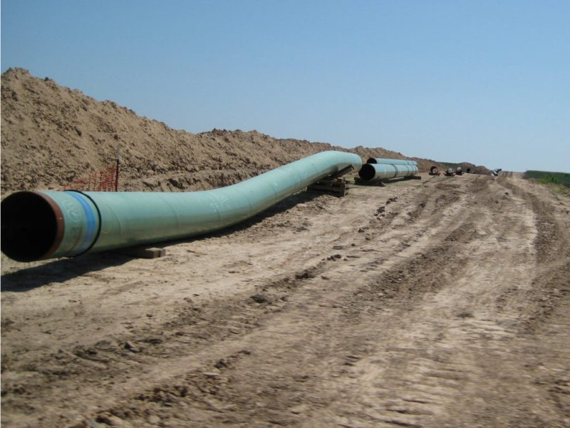 Large pipes lay along excavated ground in preparation for installation.