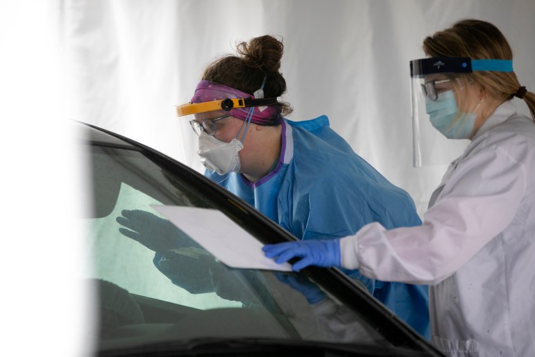 Bozeman Health employees help a patient learn how to self-sample at a drive-through COVID-19 testing site.
