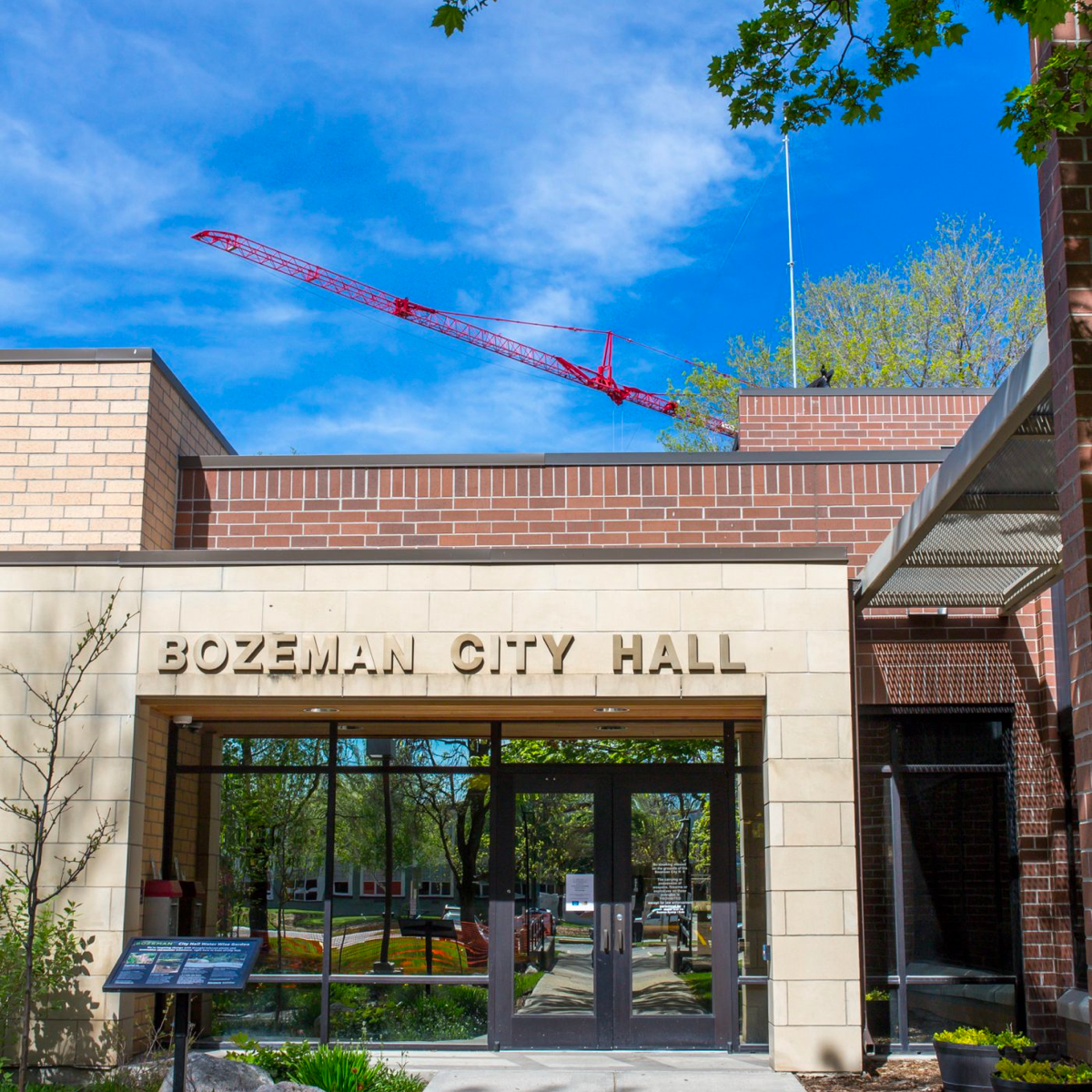 A photo of Bozeman City Hall with a large red crane rising above in the background.