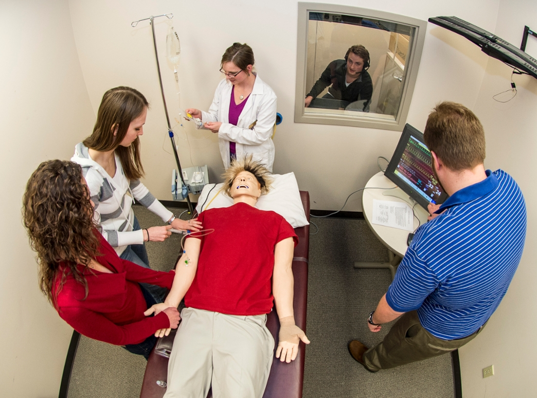 """A group of pharmacy students in an elective course work on """"Sim Man,"""" a computerized dummy that tests students by being programmed with different health scenarios."""