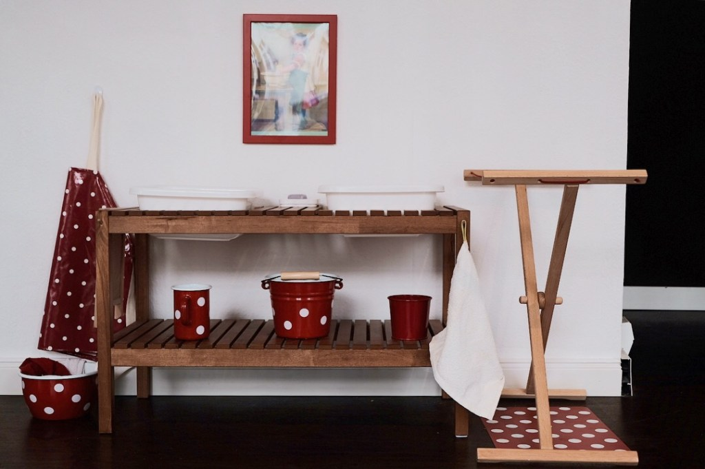 Montessori cloth washing station with a polkadot apron by montessori design by nuccia and drying rack red enamel in the prepared montessori toddler community environment