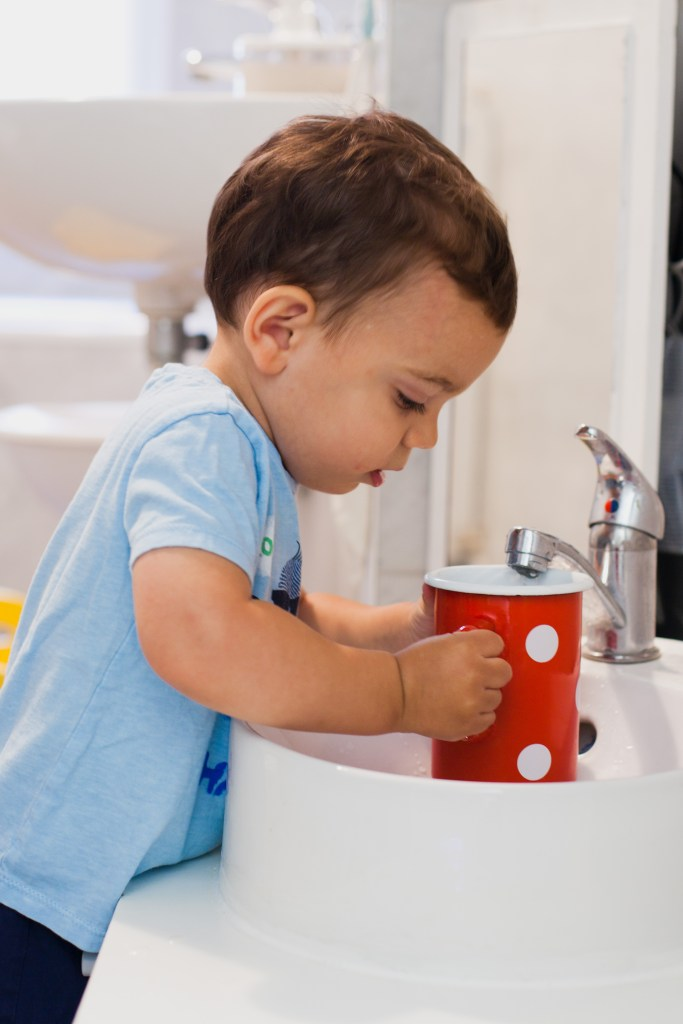 montessori toddler sink filling up red polka dot pitcher made from enamel for the practical life cloth washing table station the sink is in the prepared montessori bathroom with mini sink from ikea