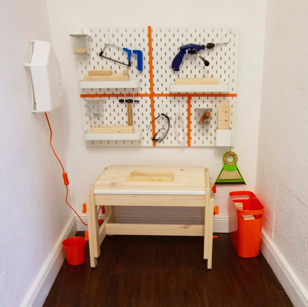 montessori woodworking station by ikea with a light and small todler tools so children can use wood and tools, saw, drill, hammer, nails, screwing, srewdriver, bamboo broom and dustpan, ikea pegboard and stool, made by montessori mother materials, the only montessori playgroup toddler classroom in germany montessori kita school in berlin