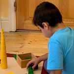 Pojke som arbetar med Montessorimaterial.
