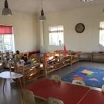 Rum i förskolan med bord och stolar samt hyllor fyllda med material.