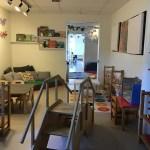 Lokal i förskolan med trappa och hyllor med material.