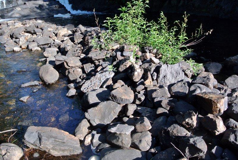Tas de pierres taillées au pied de la chute
