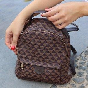 manos con mochila marrón estampada