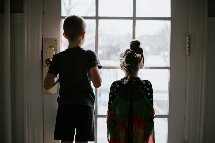 young brother and sister looking out glass door