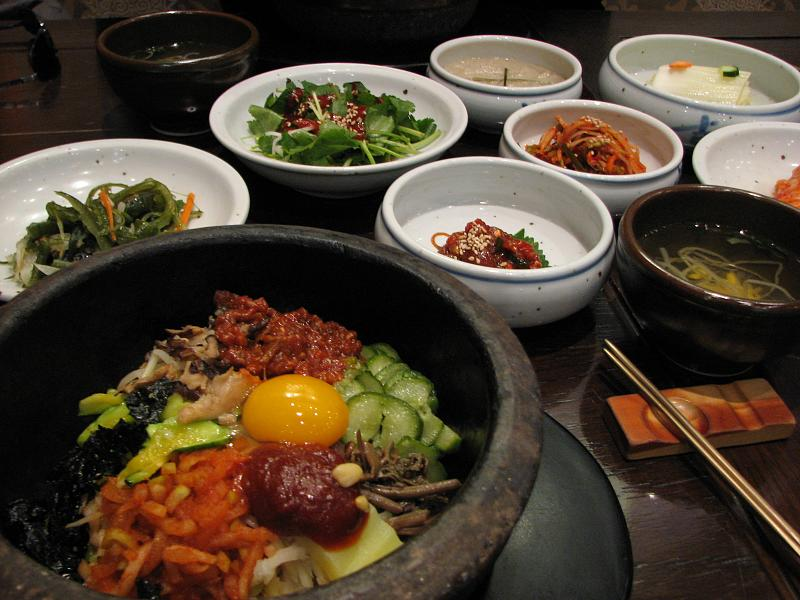 A bowl filled with vegetables and an egg yolk with side dishes.