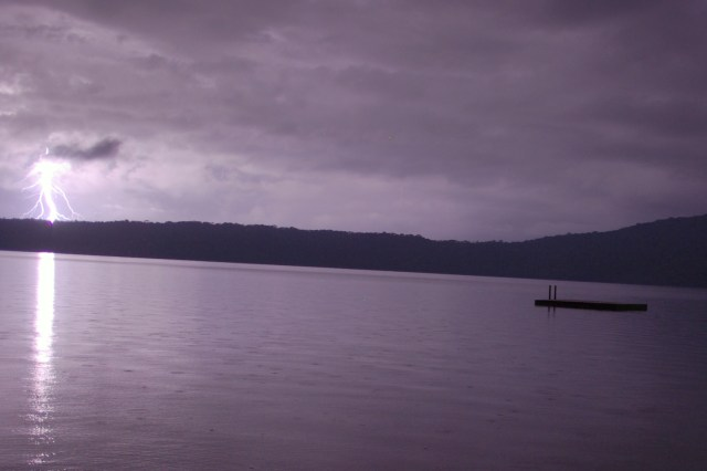 Lightning strikes far in the distance beyond the flat calm waters of the lake.