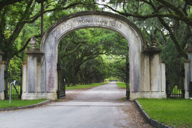 A stone arch with Wormsloe carved into it rises over a tree-lined road.