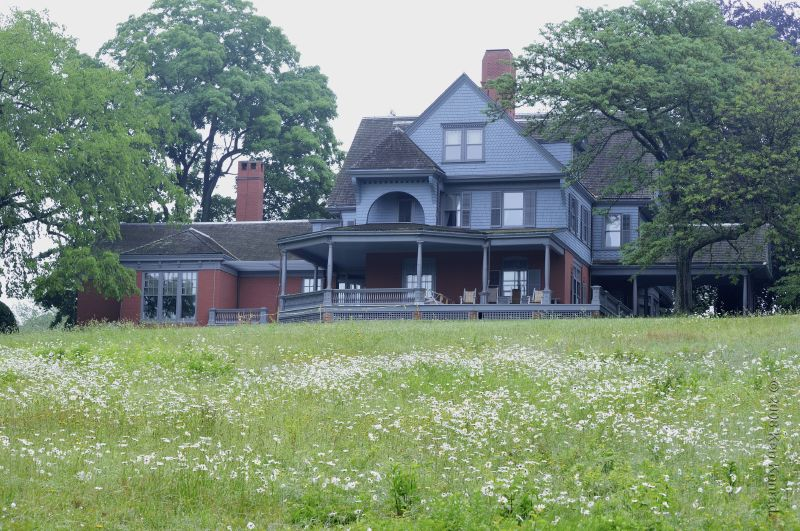 View of a multilevel Queen Anne home with an expansive lawn.