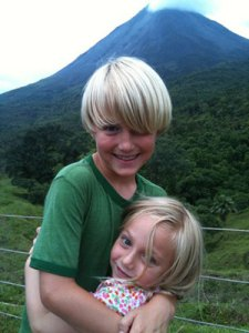 Anders and Annika hug with the dramatic view of Mt Arenal behind them.