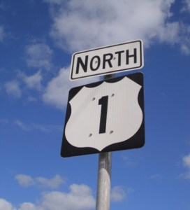 Highway 1 North road sign with deep blue sky studded with clouds.