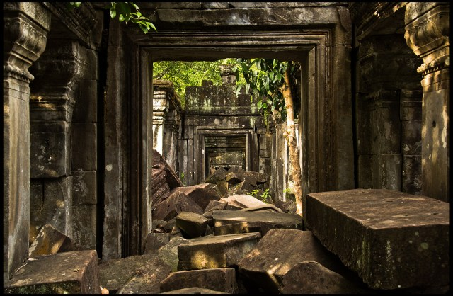 Blocky stone rubble in a temple corridor with vegetation creeping in.