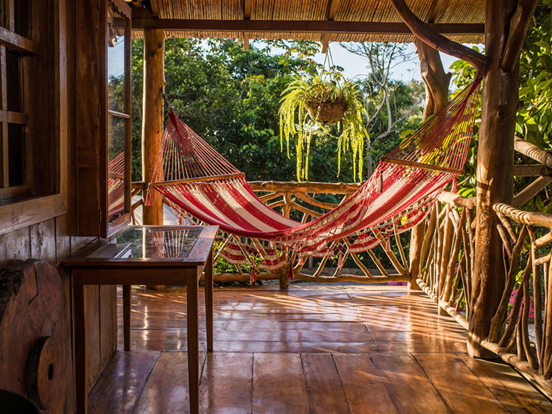 A hammock on an open air porch at La Sombra EcoLodge.