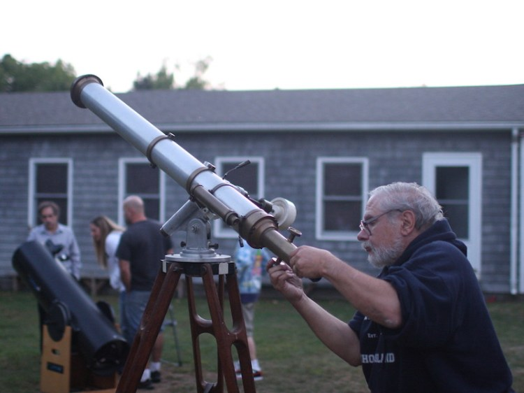 slide 2 - Adult setting up a telescope in daylight
