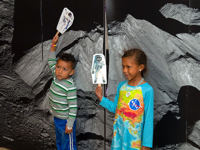 Two children holding up paper astronaut cutouts