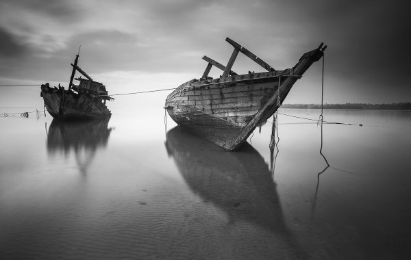 Ships on the beach in black and white with clouds on the sky