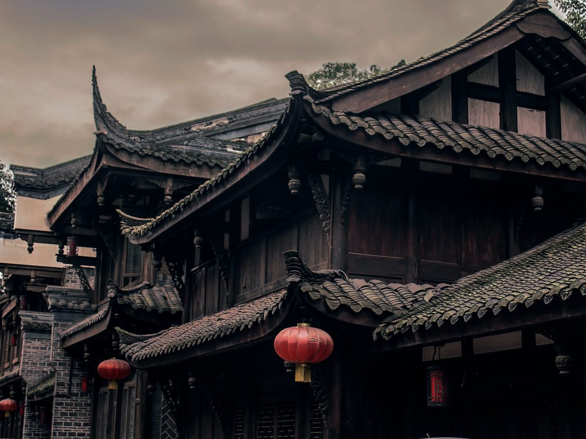 Chinese house with pointed tiled roof and chinese lanterns hanging outside