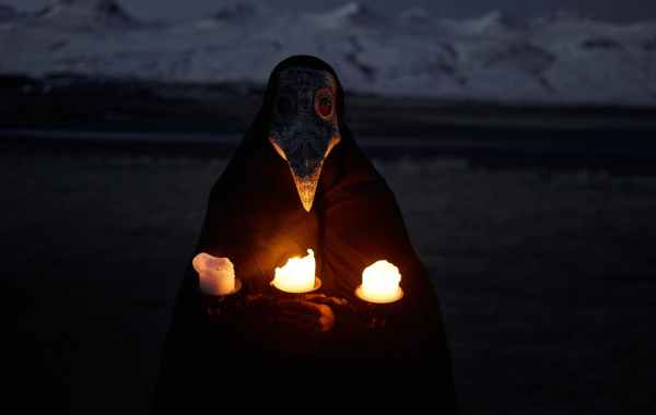 person in plague mask with burning candles at night outdoors