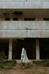 unrecognizable woman in white dress near abandoned building