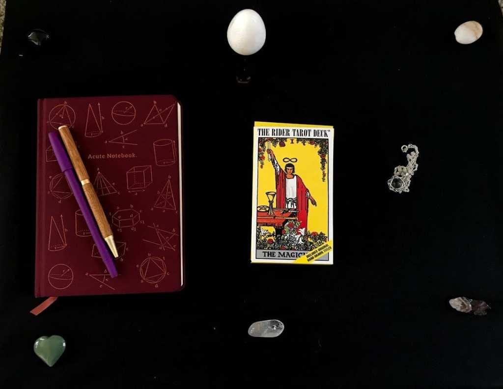 tarot deck, crystals, and pendulum with notepad