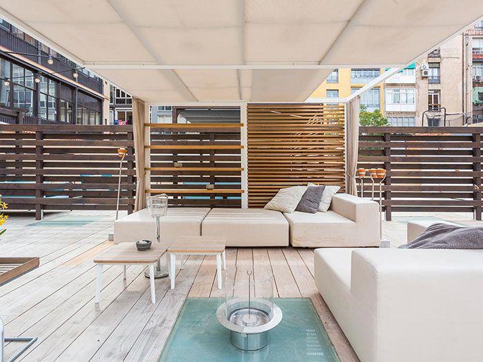 terraza con tarima de madera y sofas en atico de barcelona