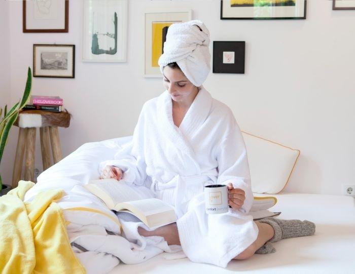mujer con albornoz en cama