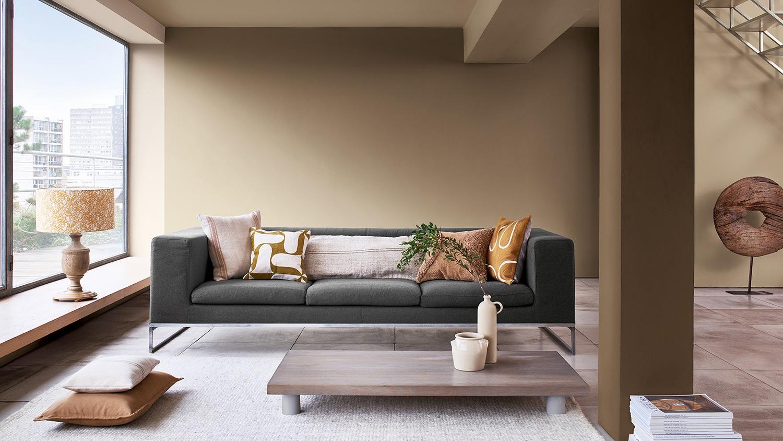 sofa gris con pared verde ocre