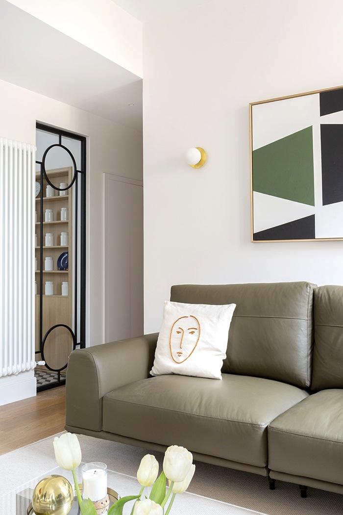 detalle sofa oscuro con cuadro geometrico salon mid century modern