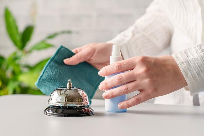 Protocolo de seguridad y sanidad en hotel donde una señora limpia el timbre