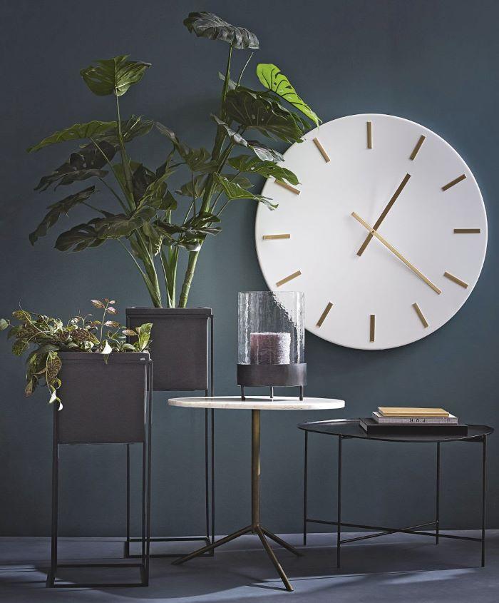 Reloj estilo vintage con decoración de plantas y mesas