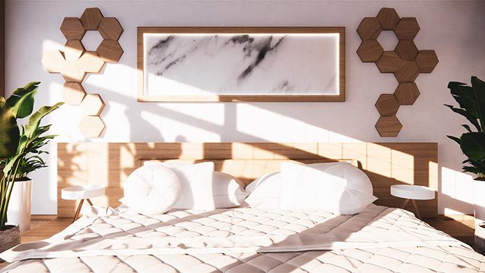 Decoración en un dormitorio con cama de matrimonio donde la luz natural entra por la ventana