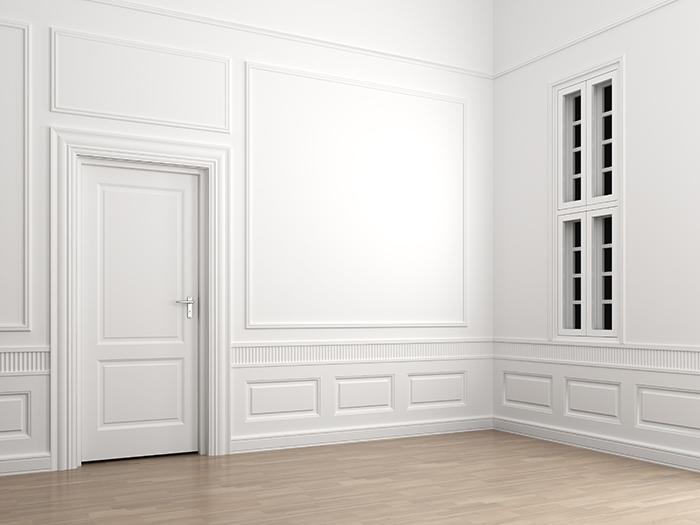 Habitación vacía de color blanco con una puerta cerrada