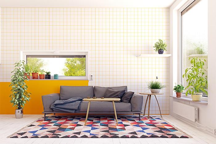 Pequeño espacio de descanso con alfombra estampada con motivos geométricos y pared decorada a cuadros mediante pintura sectorizada