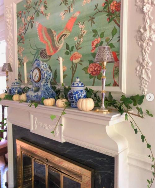 pequeño rincón con decoración británica colonial con objetos antiguos y papel print en la pared