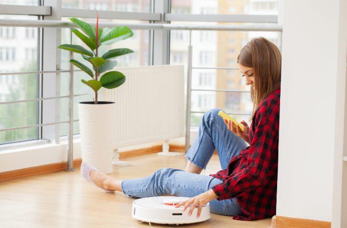 robot aspirador con chica programando para que limpie su hogar