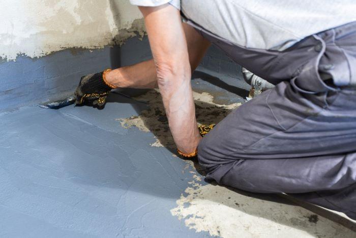 Trabajador aplicando mortero de impermeabilidad