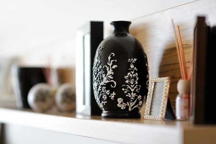 jarrón negro con dibujos florales colocado en una estantería