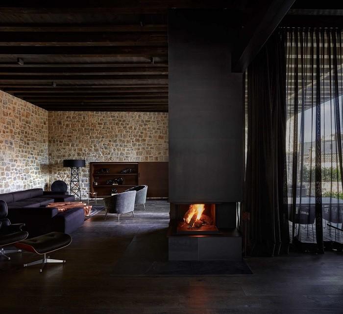 Interior de un proyecto de interiorismo rural con chimenea y materiales de madera