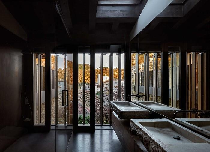 baño con lavabo de piedra y grandes ventanales al fondo para dar luz